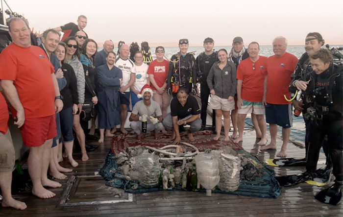 Scuba divers stand around a pile of collected ocean litter